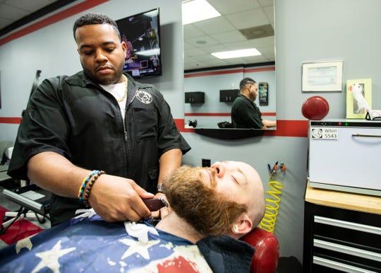 Brandon Morgan, who has has been cutting hair at A Closer Look since 2016,  trims Colman Holloway beard  on Thursday Oct. 31, 2019.