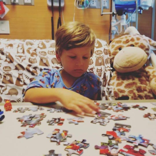 Bo Miles puts together a puzzle during a hospital stay for leukemia treatments.