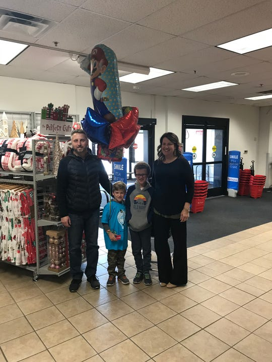 The Miles family pose for a picture before Bo begins his surprise shopping spree at the Burlington store, 1501 W. Zellman Court, Milwaukee. Pictured are (from left) Bo's father, Jason; Bo; his brother Leo; and mother, Courtney.