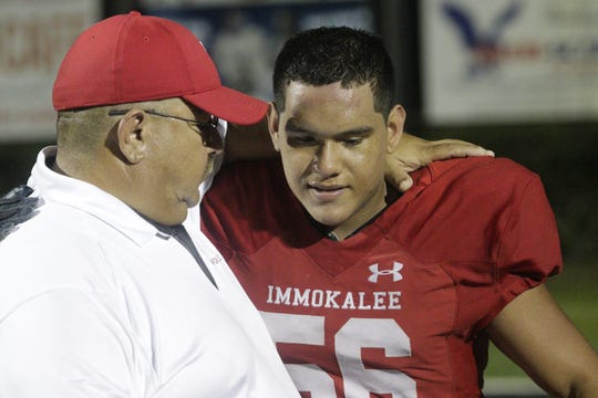 Immokalee assistant coach Izzy Gallegos embraces lineman Joseph Walker after Friday night's game against Fort Lauderdale-University. Gallegos, 50, is stepping down after 27 years of coaching.