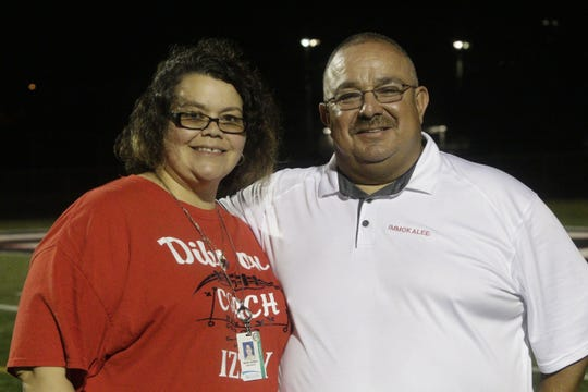 Longtime Immokalee assistant football coach Izzy Gallegos poses with his wife Wendy after Friday night's game against Fort Lauderdale-University. Gallegos, 50, is stepping down after 27 years of coaching.