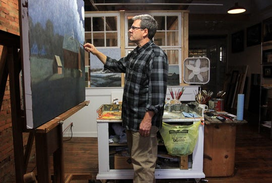 James Young works on a painting in his studio, above the Kussmaul Gallery in Granville, Ohio.