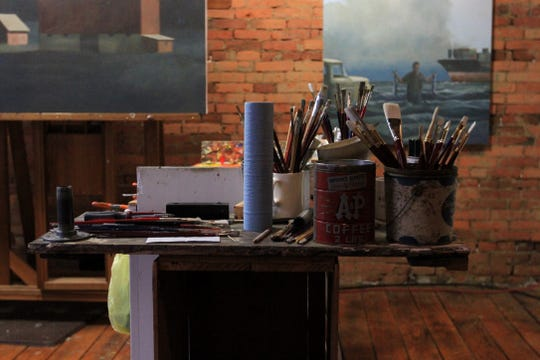 Paintbrushes and supplies at a work station in James Young's studio, above the Kussmaul Gallery in Granville, Ohio.