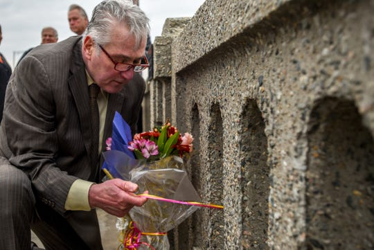 Robert Popp places flowers next to the plaque honoring his sister Gloria Jean Popp in Ridgefield Park on Thursday November 7, 2019. Fifty years after Gloria Jean Popp was killed in a car accident as she walked over the Route 46 Bridge over the Hackensack River, the bridge walkway is dedicated in her honor.