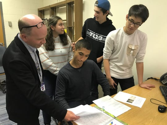Ramsey High School teacher Keith Lyle goes over the morning announcement routine with student volunteers Lucy Latorre, Max Nokes, Joaquin Kull and Brandon Hwang.