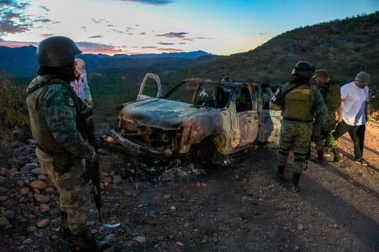 Elementos de la Guardia Nacional inspeccionan el auto de la familia LeBaron que fue calcinado.