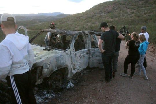 Miembros de la familia LeBarón observan este miércoles un vehículo calcinado donde fueron ultimados sus familiares cuando circulaban por las comunidades de Bavispe y Ejido Pancho Villa el lunes, al filo de medio día durante el ataque de un grupo armado.