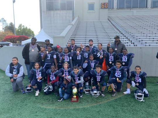 The Poughkeepsie 9-and-under football team poses with its coaches at West Point last Sunday after winning the Taconic Youth Football championship.