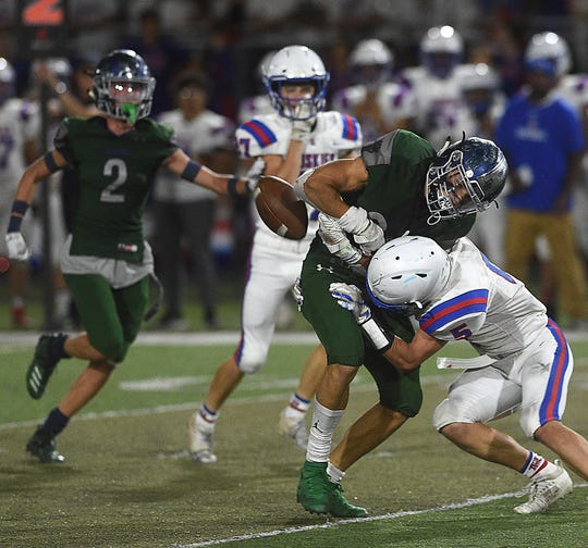 Reno's Drue Worthen (5) forces a fumble with a hit on Damonte Ranch's Ashton Hayes (26) during their football game at Damonte on Sept. 13, 2019.