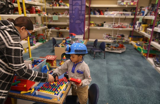 Josiah Cason, 4, gets a helping hand from mother Iris Roman, Rochester, as he plays with a tool set at the Toy Library, located inside the Rochester Public Library Lincoln Branch on Joseph Avenue Wednesday, Nov. 6, 2019.  The Toy Library is celebrating completed renovations with a carnival-themed party on Saturday, Nov. 9, from 12:30-3:30 pm.