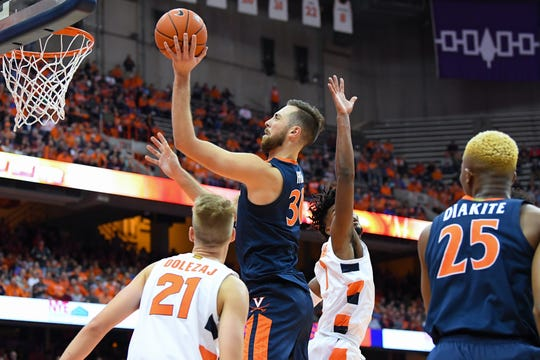 Jay Huff #30 of the Virginia Cavaliers shoots the ball between Marek Dolezaj #21 and Quincy Guerrier #1 of the Syracuse Orange during the first half at the Carrier Dome on November 6, 2019 in Syracuse, New York.