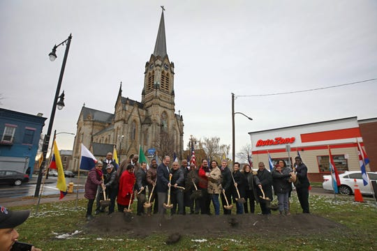 Dirt is sent flying as Rochester Mayor Lovely Warren, eighth from right, is joined by dignitaries and guests for the official groundbreaking during ceremonies for La Marketa community plaza on the lot at 828 N. Clinton Ave. in Rochester Thursday, Nov. 7, 2019.