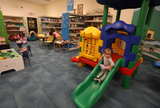 Esme LaScelle, 3, takes a doll down a slide as she plays with her grandmother, Judy Molner, not pictured, at the Toy Library, located inside the Rochester Public Library Lincoln Branch on Joseph Avenue Wednesday, Nov. 6, 2019. The Toy Library recently completed renovations that included new carpeting, new windows, and the installation of a giant interactive play set, complete with slide.