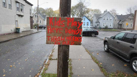 """A sign put up on Roth Street says """"Kids Play Here Do Not Throw Needles In Yard,"""" in Rochester Thursday, Nov. 7, 2019."""