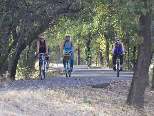 Bicyclists take a fall ride along the Sacramento River Trail on Thursday, Nov. 7, 2019, near where the Caldwell Park expansion project is planned.