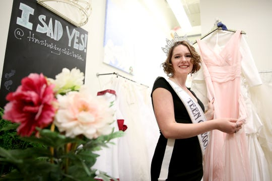 """Mikayla Wood, 17, of Scio, stands with a dress she has collected for the """"Be-You-tiful"""" Prom Dress Giveaway that will be held April 4, 2020. Wood is organizing the free event for any high schooler in Oregon and partnering with local dress shops. Photographed at Shabby Chic Bride consignment shop in Salem on Nov. 6, 2019."""