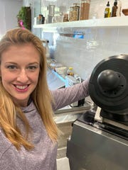 Jessica Tyler Comegys shows off her cold press juice machine at her new eatery, Glow Alchemy Kitchen.
