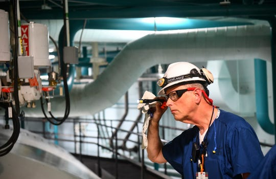 U.S. Nuclear Regulatory Commission resident inspector Donald Krause uses a flashlight to look at valves and equipment Wednesday, Nov. 6, 2019, at the Monticello Nuclear Generating Station.