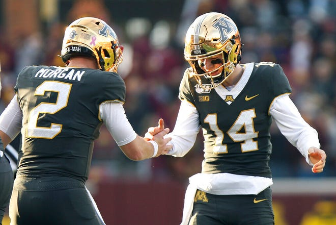 Minnesota quarterback Tanner Morgan (2) celebrates with teammate Casey O'Brien (14) after their team scored a touchdown against Maryland during an NCAA college football game Saturday, Oct. 26, 2019, in Minneapolis.