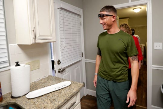 Army Specialist Derek Taylor smiles as he sees the little details scattered throughout his new home. The home was gifted to him mortgage-free by Building Homes for Heroes on Thursday, Nov. 7, 2019.