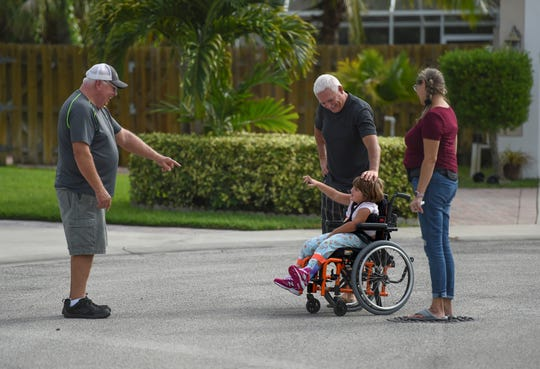 """Neighbor Larry Engleman (left) enjoys a morning greeting with Maci during her morning walk with her adopted parents Darin and Lisa Jones Wednesday, Nov. 6, 2019, in the Compass Pointe neighborhood of Indian River County. """"She's a sweetheart, I'll tell you that,"""" said Engleman. """"She's wonderful, she's getting better all the time, impressed how far she's come along. A cute little girl."""""""