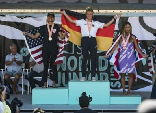 Zoe Benedetto, left, shares the podium with her silver medalist finish at the ISA World Junior Surfing Championship.