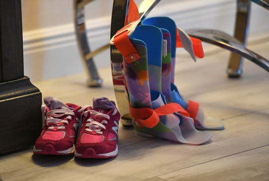 """The shoes and leg braces for Maci sit on the floor of the living room at the Jones's home, where they spend most of their time, playing, exercising and watching movies together. The braces, an insert for her feet to keep them flat, and the outer brace for her ankle and leg, slide inside the shoes to help her while walking. """"It's difficult, because there's times when she doesn't want them on, but her feet are starting to turn out , and she has to wear them, It's challenging,"""" Darin Jones said."""