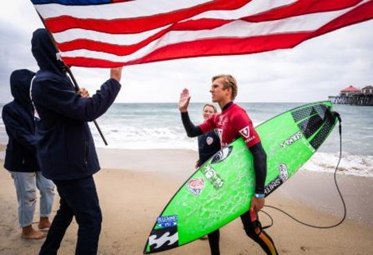 Tommy Coleman of Vero Beach is congratulated on the beach after helping Team USA win the gold medal at the ISA World Junior Surfing Championship in Huntington Beach,. Calif.