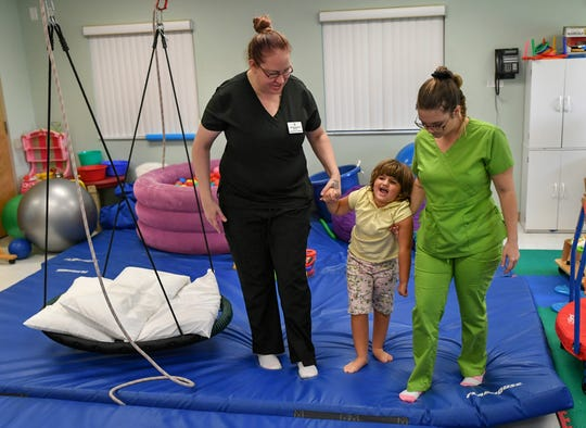 """Occupational therapist Joelene Newman (left) and pediatric technician Brianna Pesce (right) work with Maci Jones on walking during one of her many therapy sessions at Sunshine Physical Therapy Clinic on Wednesday, Nov. 6, 2019, in Vero Beach. """"It's good, I see improvements, but I don't work with her all the time, but the coordination with her hand is getting better the more we do,"""" Newman said after an exercise to improve dexterity in Maci's left hand. """"She's very fun, a happy kid."""" Maci's adopted parents, Darin and Lisa Jones, take Maci to Sunshine Physical Therapy Clinic three times a week for physical and speech therapy due to the nature of Maci's injuries."""