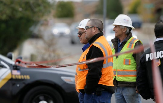 Construction workers who were working in the area of an officer involved shooting Thursday stand outside the police tape waiting to return to their worksite.