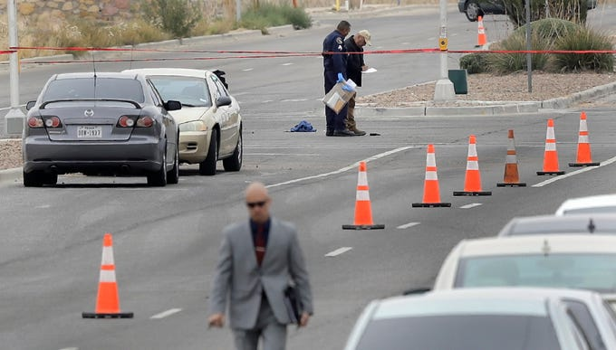 Officers stand over a hand gun in the intersection of Pebble Hills Blvd. and Rich Beem Blvd. Thursday after an officer was involved in a shooting.