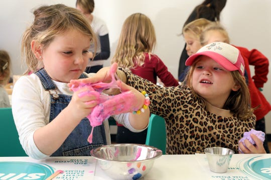 """Stella Mulhearn, right, of Larchmont feels her sister Millie Mulhearn's slime at D.I.Y. Slime in Larchmont Nov. 6, 2019. The 5-year-olds picked their own slime colors and add-ons at the shop, where the slogan is """"leave your mess here,"""" allowing families to enjoy making slime while not having to clean up."""