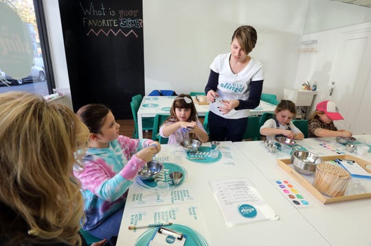 """Co-owner Stacey Sarver helps customers make slime at D.I.Y. Slime in Larchmont Nov. 6, 2019. The slogan for the shop is """"leave your mess here,"""" allowing families to enjoy making slime while not having to clean up."""