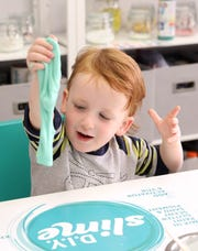 """William Smith, 3, of Larchmont plays with his slime at D.I.Y. Slime in Larchmont Nov. 6, 2019. The slogan for the shop is """"leave your mess here,"""" allowing families to enjoy making slime while not having to clean up."""