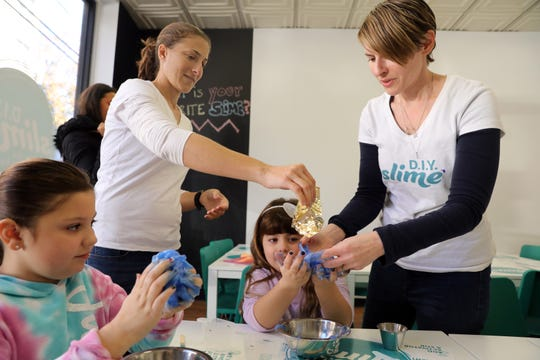 Co-owners Nicole Fiftal, left, and Stacey Sarver help Vanessa Faella, 5, of New Rochelle add gold leaf to her slime as sister Brianna, Faella, 7, works on mixing hers at D.I.Y. Slime in Larchmont Nov. 6, 2019.
