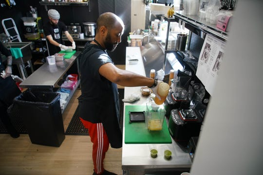Jason Aviles, a co-owner of Green Box Kitchen, prepares a freshly made drink for customers visiting the first brick and mortar shop on the corner of Fourth and N. Market St.