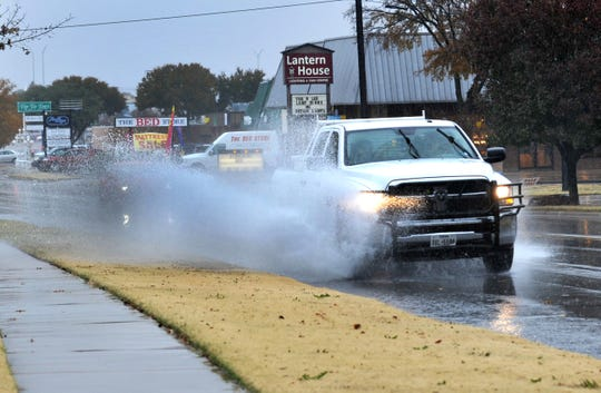 A pickup truck sloshes through the deep part of Southbound McNiel Ave. after most of Wichita Falls received much needed Wednesday into Thursday overnight Rain.
