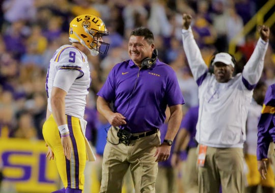 LSU quarterback Joe Burrow celebrates with coach Ed Orgeron during the fourth quarter against Florida at Tiger Stadium.