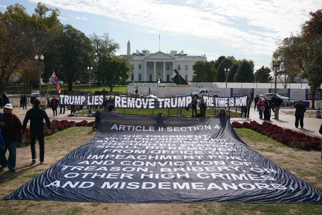 Activists hold a banner asking for the impeachment of President Donald Trump on Nov. 5, 2019 in front of the White House in Washington, DC.