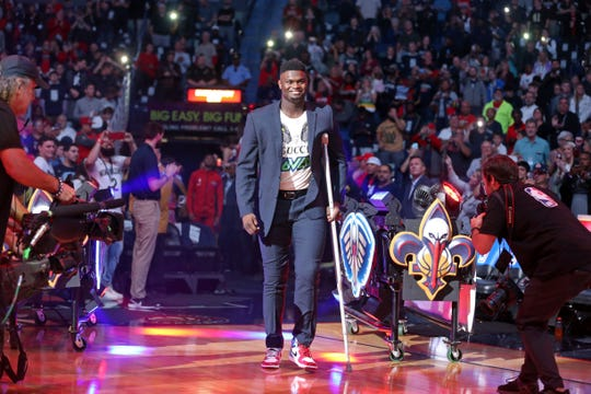 Still recovering from knee surgery, Pelicans forward Zion Williamson takes part in team introductions before an October 25 game against the Mavericks.