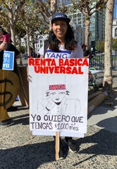 Eliana Jaramillo holds a sign in support of Democratic presidential candidate Andrew Yang's proposal for a universal basic income, which would grant everyone $1,000 a month to help cover basic expenses. She says this sort of monthly stipend would have helped her and her young children leave an abusive relationship sooner.