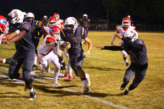 Marksville's Braydon Flores (1) looks to pick up positive yards against Caldwell Thursday.