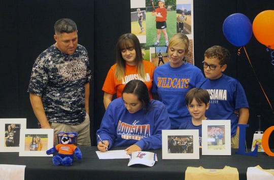 Leesville first baseman Bella Houck (center) signs with Louisiana College Monday.