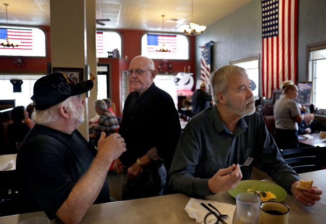 Veterans Dan Nagan (Vietnam) on left and Ken Coenen (Korea) in center, have a conversation while, friend David Rolfs eats breakfast at the Old Glory Cafe in Kimberly.