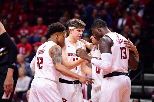 Paul Mulcahy (center) and Jacob Young (left) talk with Rutgers teammates against Bryant.