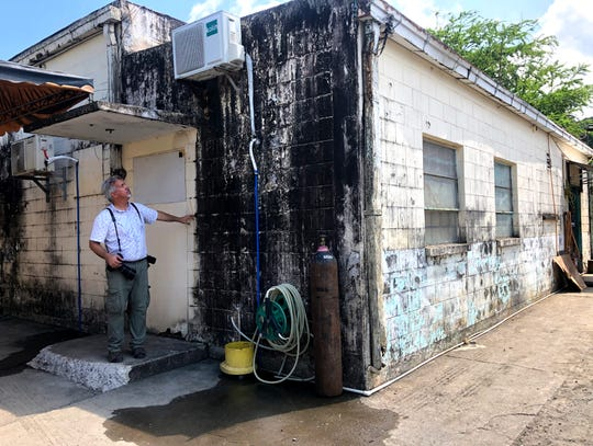 Photojournalist Ron Erdrich stands beside the building that once was Fleet Audio-Visual Command Pacific, Philippines at Naval Air Station Cubi Pt. Thirty years later, the building is now home to a warehousing office and the base has been transformed into an economic zone.