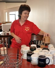 Tammy Reese, owner of The Flipping Egg, shows some of the coffee cups that customers leave at the restaurant for use.