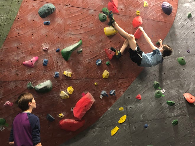 A climber attempts a route on a bouldering wall at Island Rock Gym on Bainbridge Island.