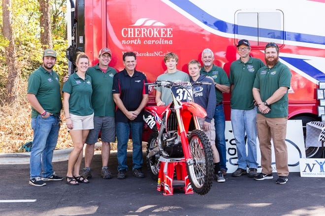 Black Mountain Home resident Johnny, center, receives a dirt bike from Honda, which was donated through Makson, Inc. owner David Eller, left of center.