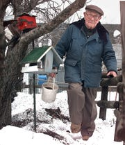 Edward Baker Sr., 91 of Essex Junction heads out into his yard to fill some of his homemade bird feeders on Feb. 23, 2000.